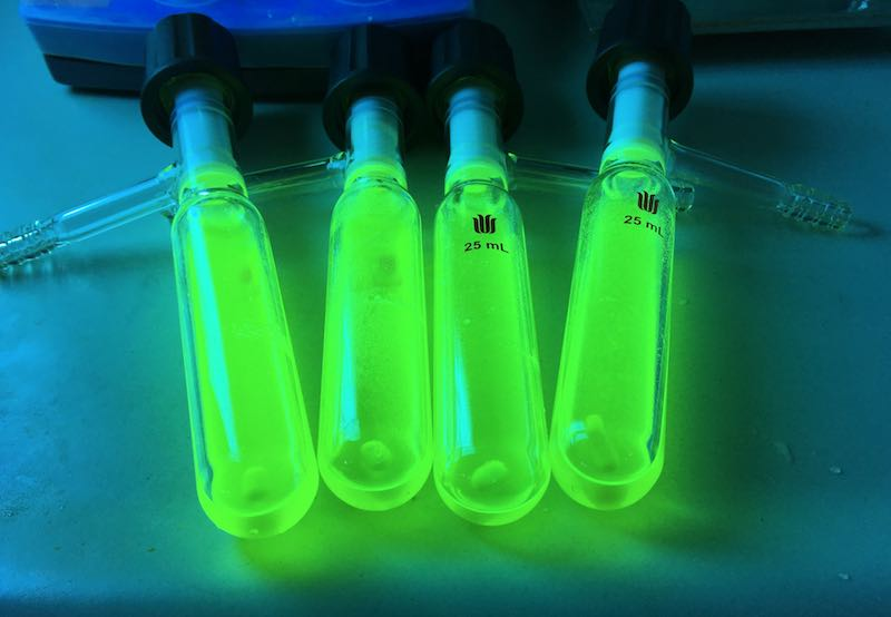 CuPCP compound glowing in vials under UV light.