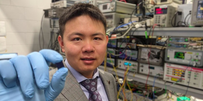 Dr. Xingyuan Xu with the microcomb chip