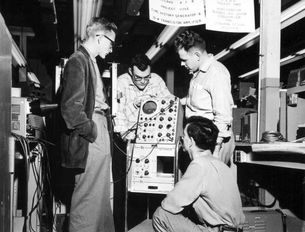 Employees at Radiation Inc. standing around an oscilloscope
