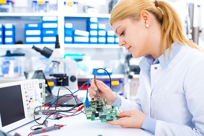 An engineer solders a circuit.