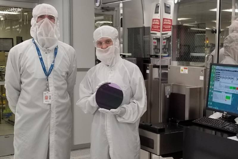 MIT researchers holding silicon wafer.