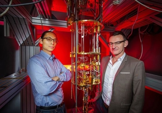 Researchers from UNSW Sydney stand beside a dilution refrigerator