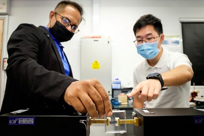 Researchers with a terahertz chip utilizing PTIs