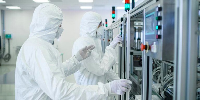 Semiconductor manufacturing employees wearing personal protection equipment