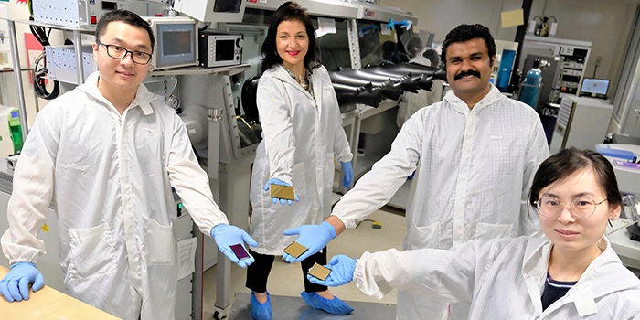 Team of NTU Singapore researchers holding scaled up perovskite solar cells