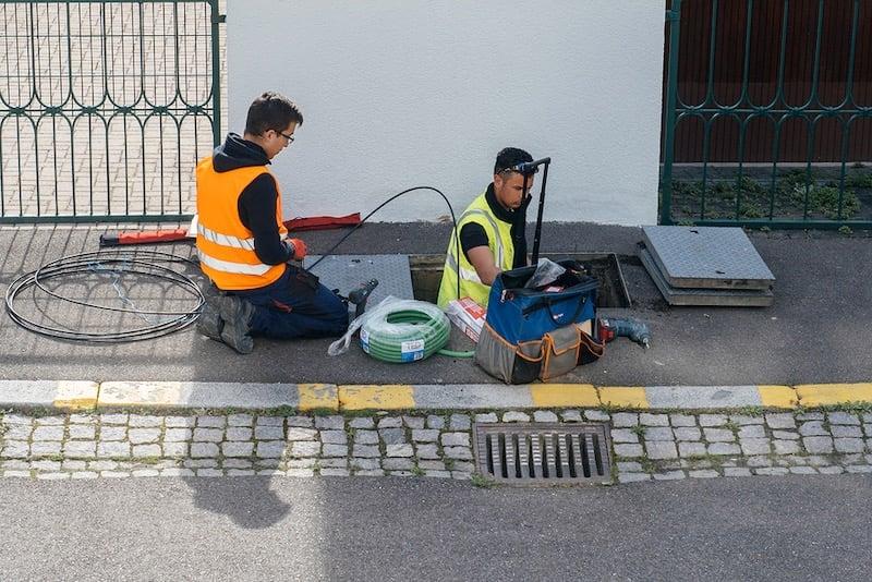 Two telecom employees lay fiber optics cables.