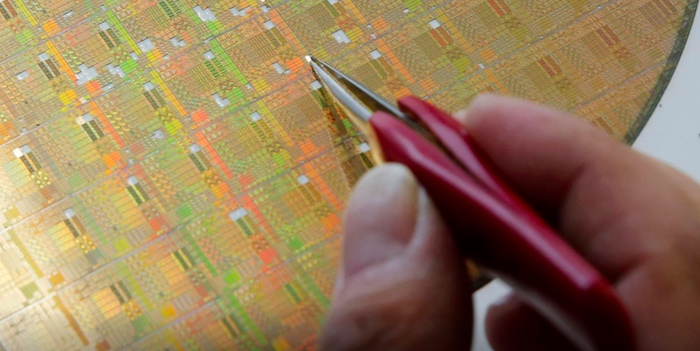 Researcher gestures to a wafer while designing semiconductor project